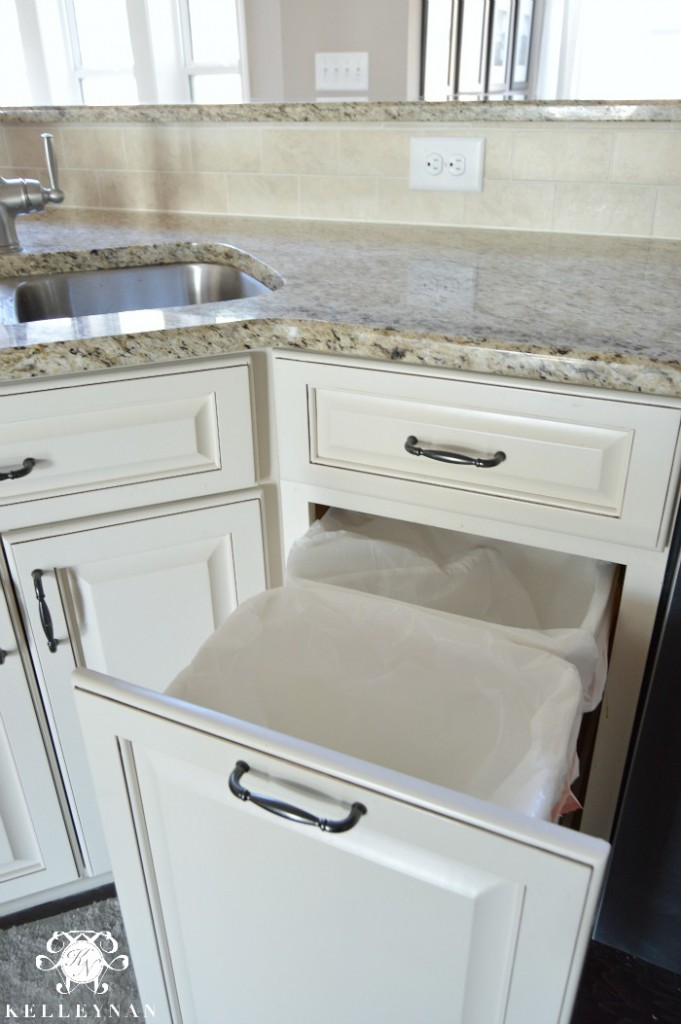 Pull out trash can in white cabinet