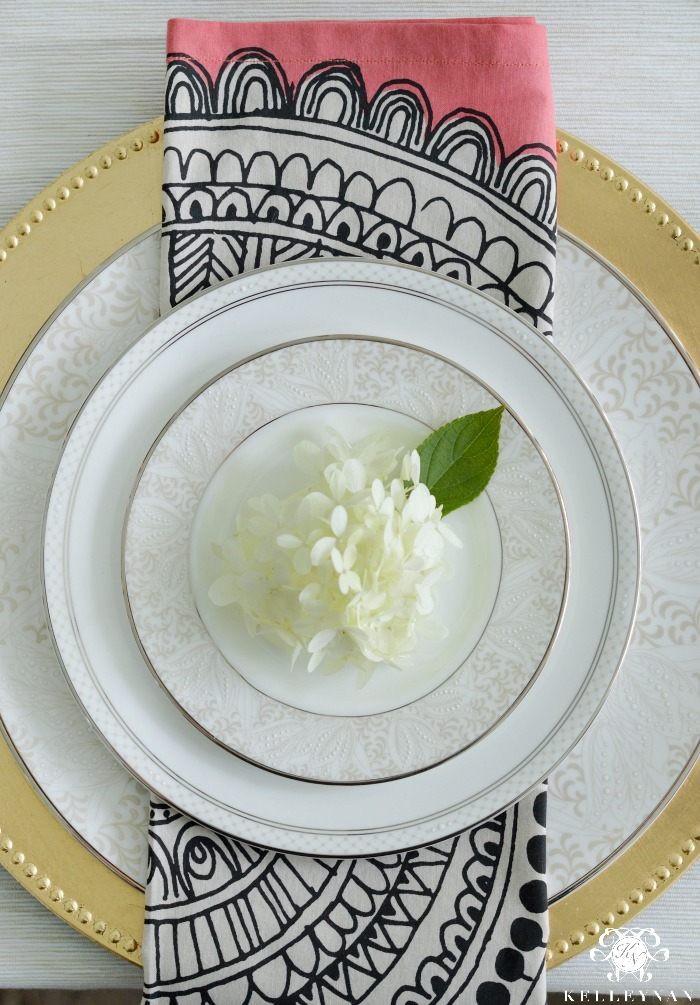 Black and White and Pink Crate and Barrel Napkin on Gold Charger for Place Setting with White Hydrangea Bloom