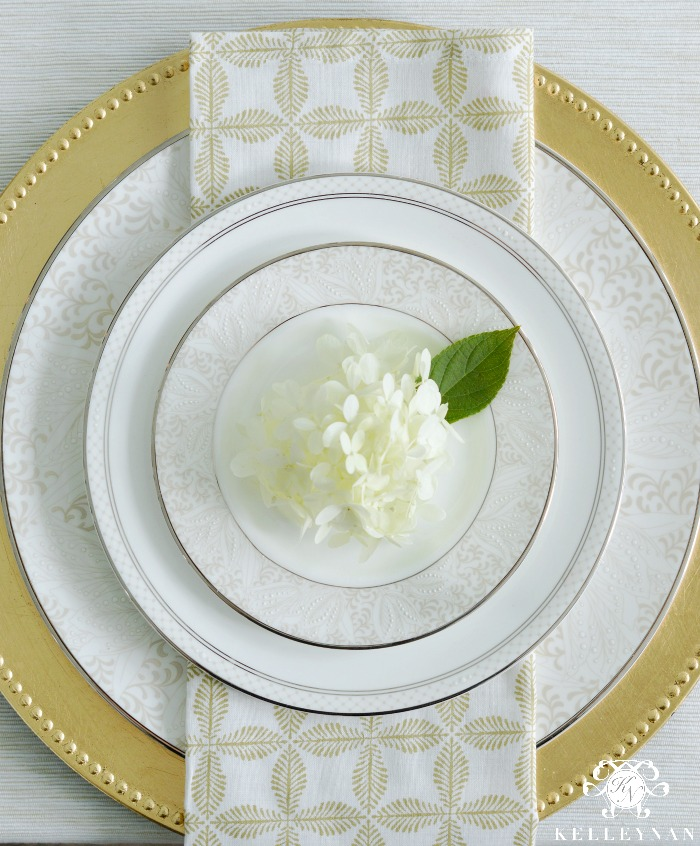 Place Setting with Gold Beaded Charger and plates with napkin and hydrangea bloom