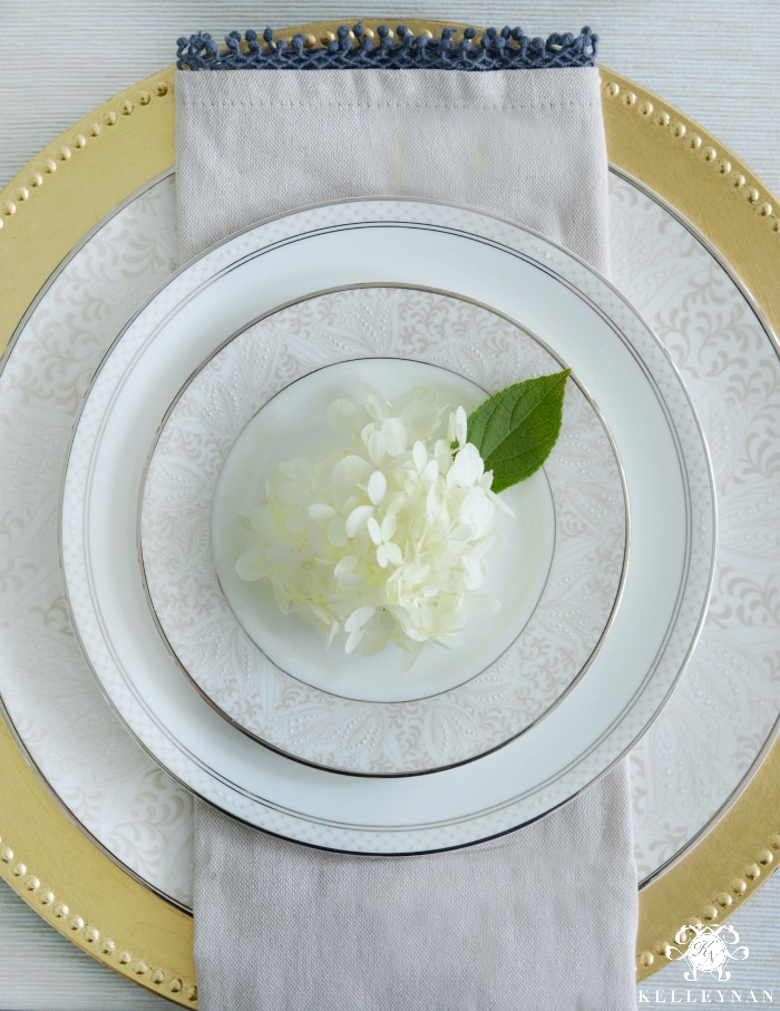 Place setting with napkin and gold charger with world market napkin and hydrangea