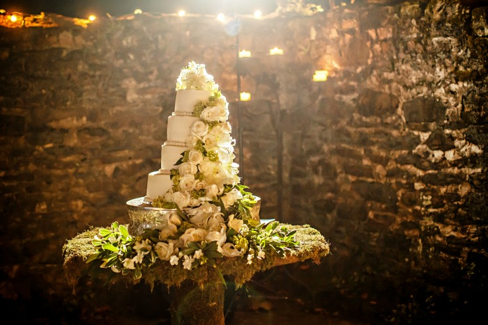 white-wedding-cake-with-cascading-roses-and-flowers-on-moss-table