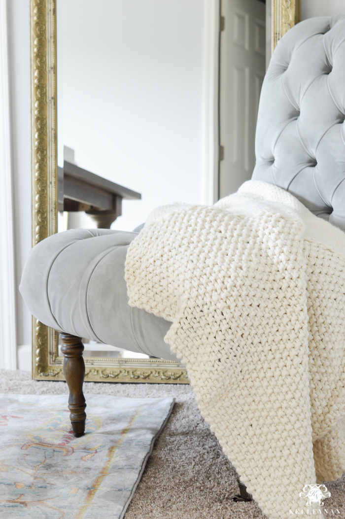 gray-tufted-slipper-chair-for-office-with-leaning-gold-mirror