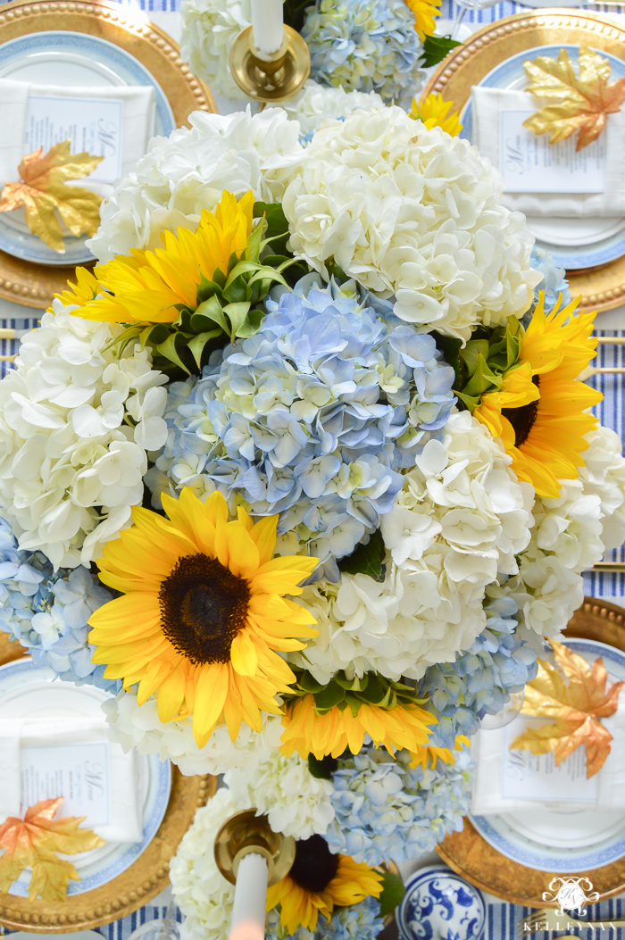 hydrangea-and-sunflower-centerpiece-on-thanksgiving-table-with-blue-and-white-and-gold-setting-1-of-1