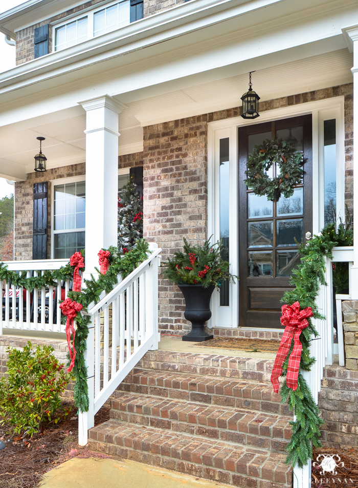 classic-traditional-christmas-red-bows-and-greenery-garland-on-front-porch-with-columns-urns-with-greenery-and-berries