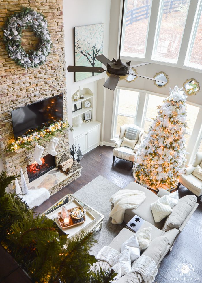 two-story-christmas-great-room-with-stacked-stone-fireplace-neutral-decor-with-silver-white-and-gold-tv-above-fireplace