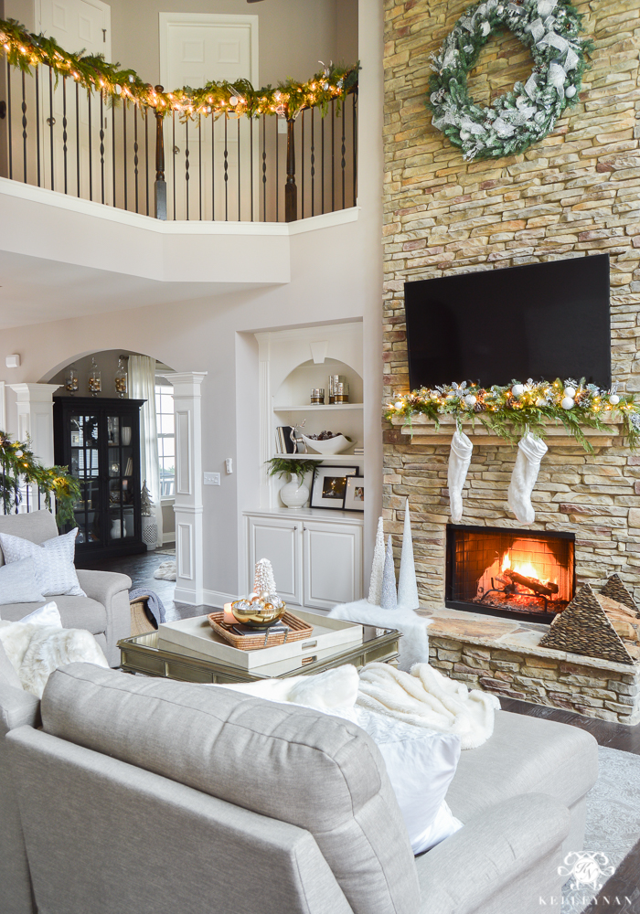 two-story-great-room-with-large-wreath-hanging-on-stacked-stone-fireplace