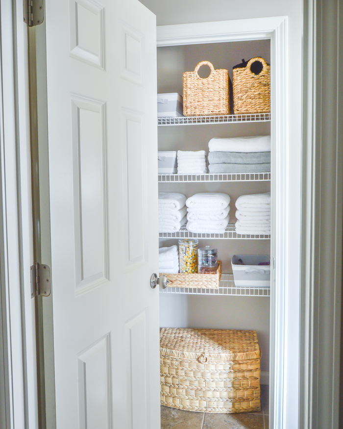 Organized bathroom linen closet with baskets and white towels