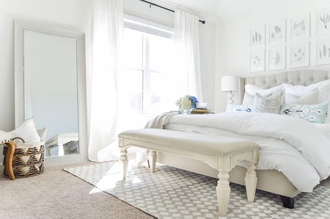 White guest bedroom with white linens and basket for pillows