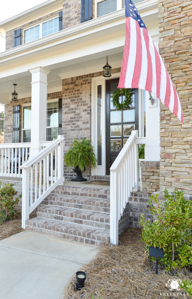 Spring Decorated Rocking Chair Front Porch with American Flag hanging at steps