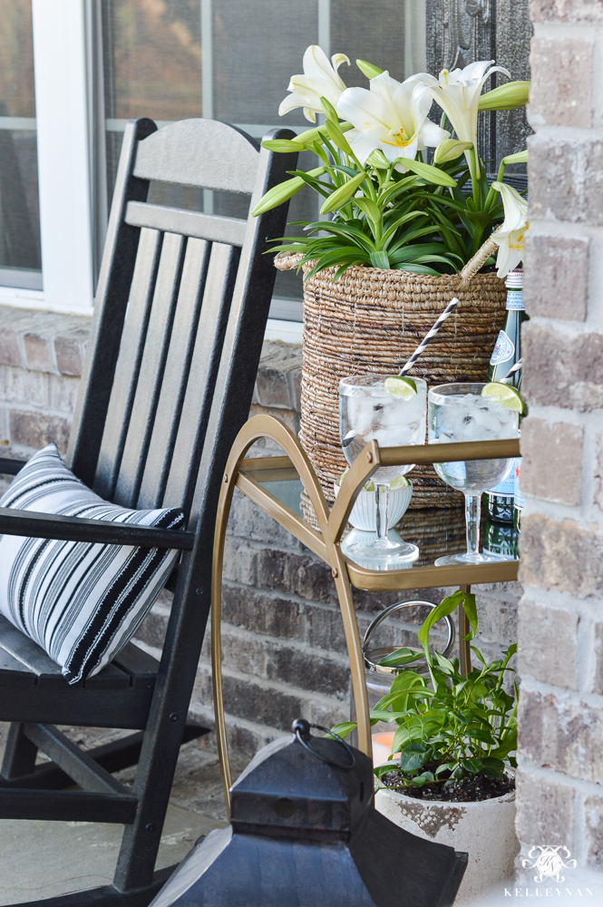 Spring Decorated Rocking Chair Front Porch with a Gold Bar Cart with plants and drinks