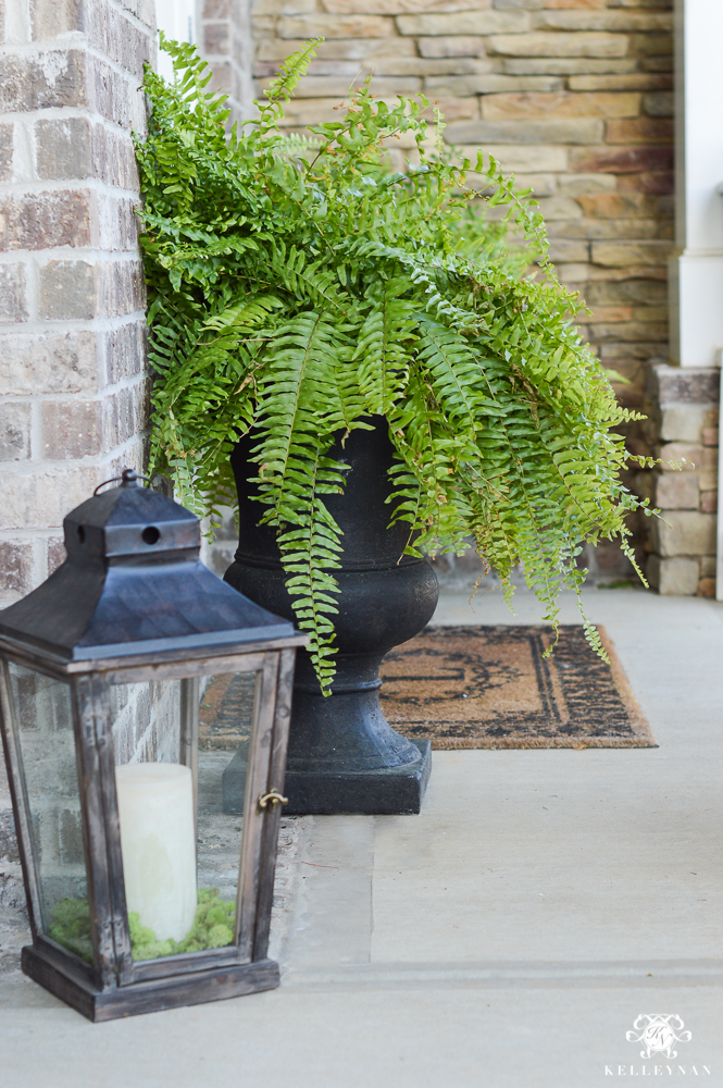Spring Decorated Rocking Chair Front Porch with lantern next to fern in urn