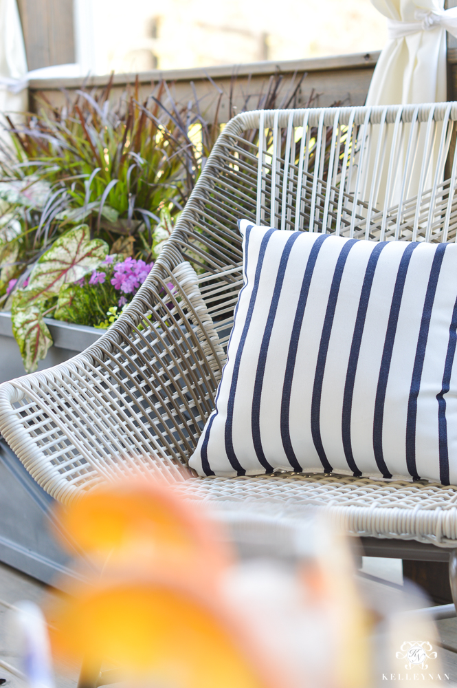 World Market woven gray chair on the porch with blue and white pillow