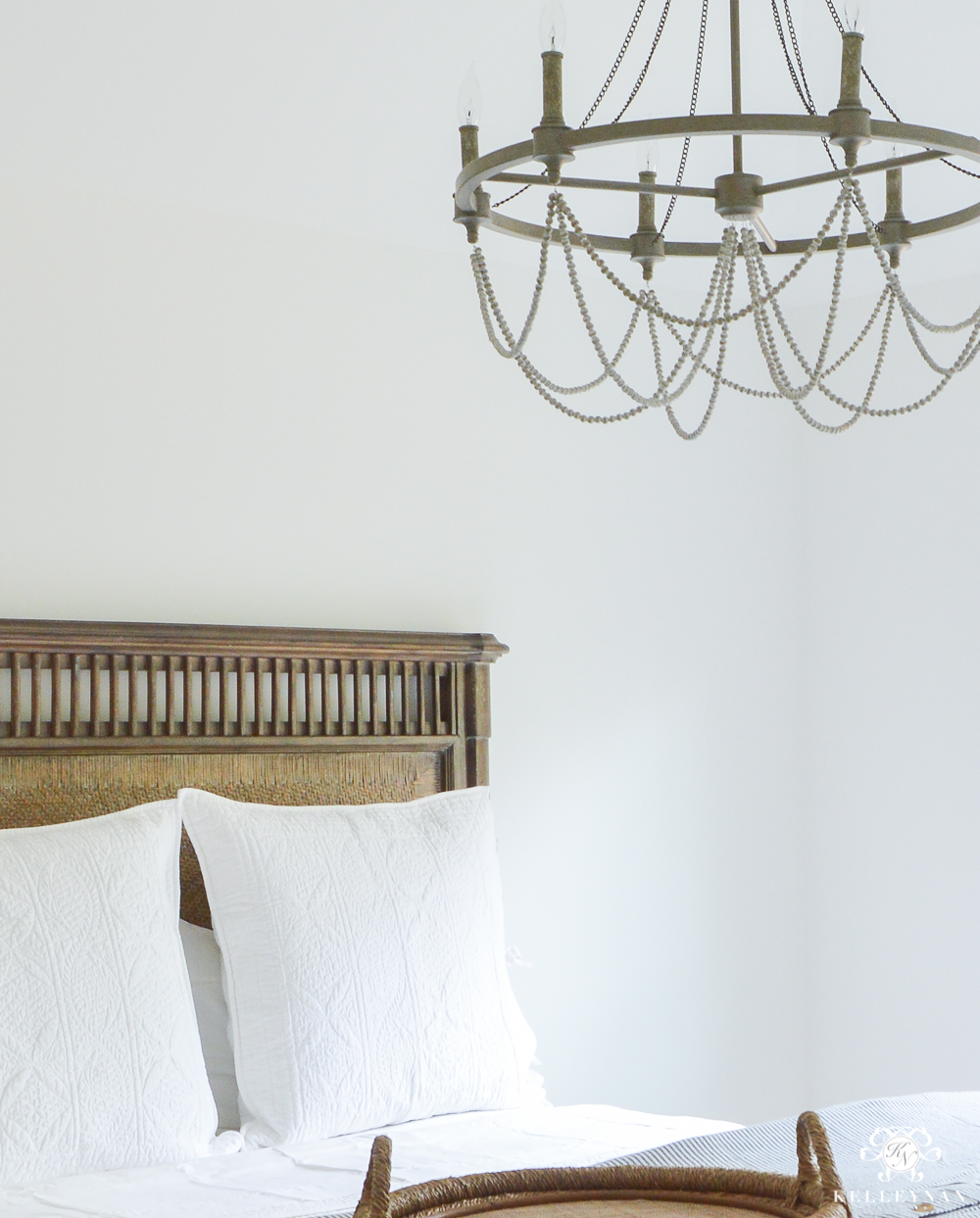 guest bedroom wooden woven cane bed with white pottery barn bedding and a chandelier