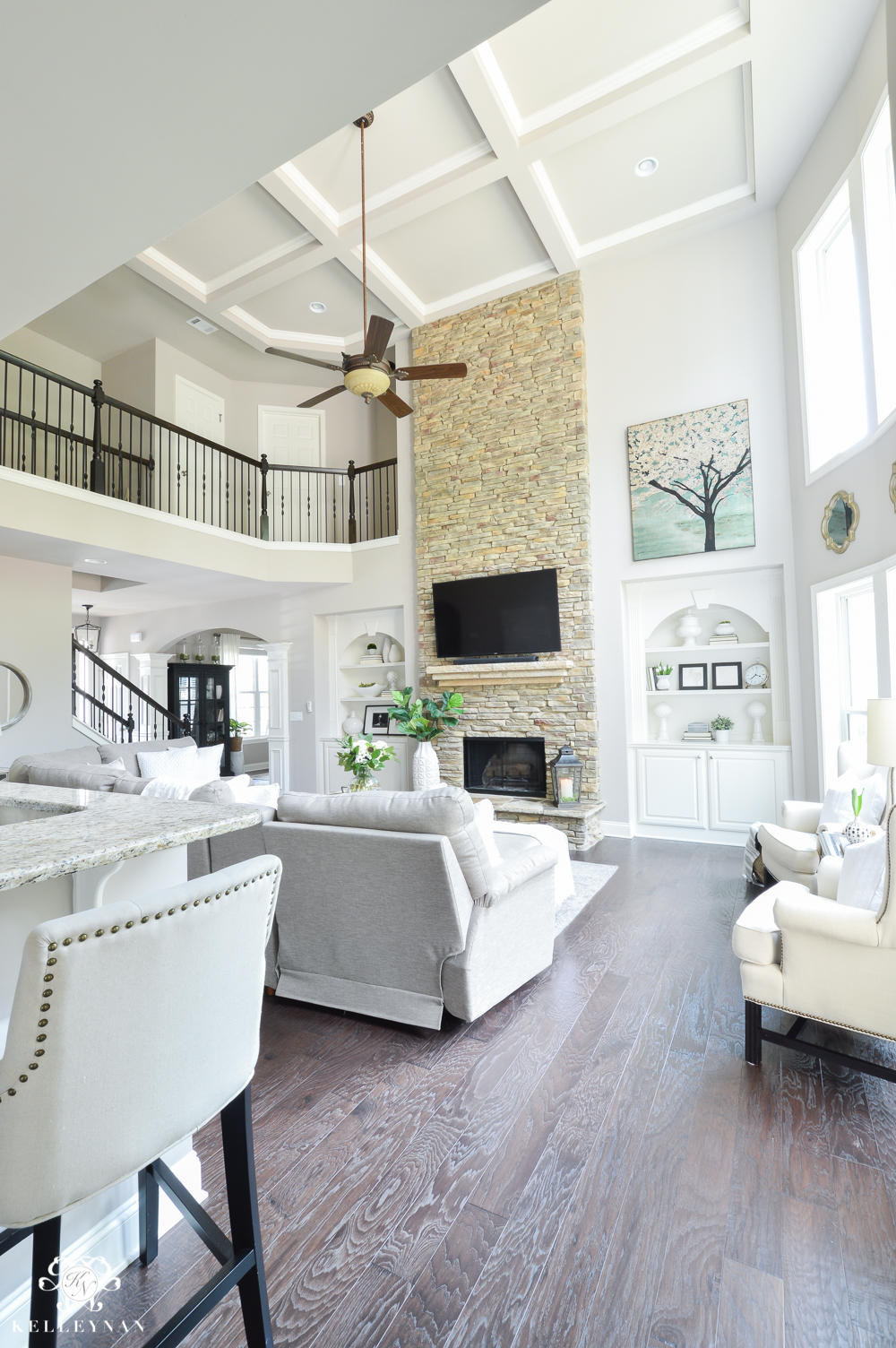 Shades of Summer Home Tour with Neutrals and Naturals- Two story living room with coffered ceiling and stacked stone fireplace with builtins