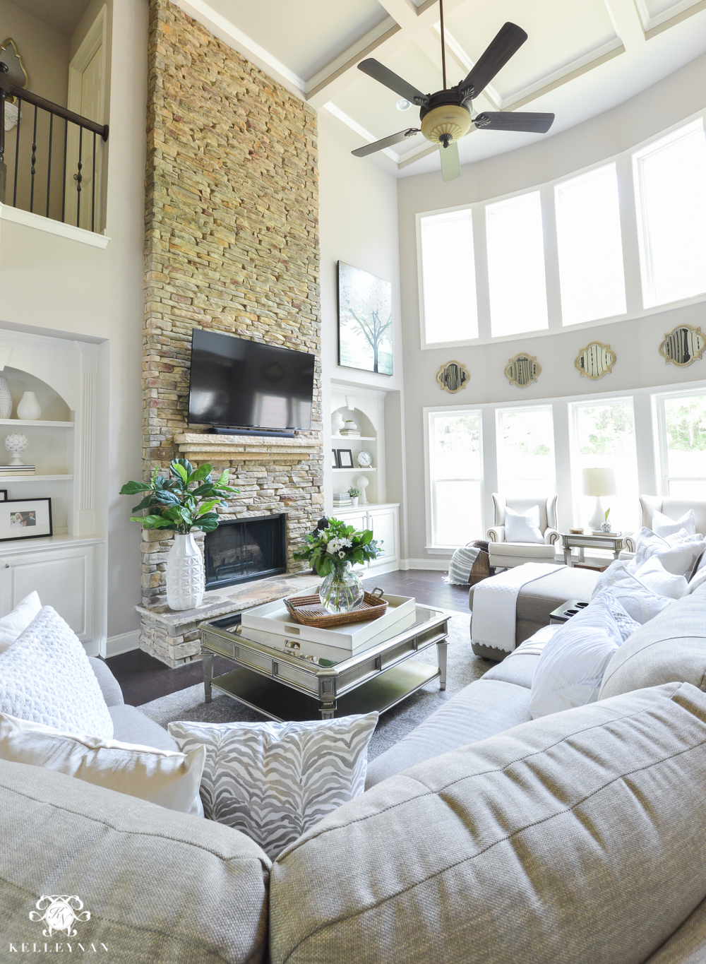 Shades of Summer Home Tour with Neutrals and Naturals- Two story living room with stacked stone fireplace and lazboy sectional