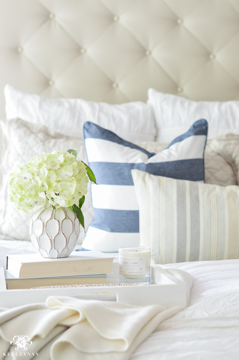 Shades of Summer Home Tour with Neutrals and Naturals-nautical blue and white striped pillows on cream tufted bed
