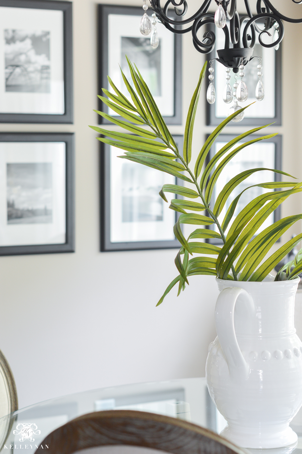 Shades of Summer Home Tour with Neutrals and Naturals- palm leaf centerpiece in vase with black and white travel gallery wall