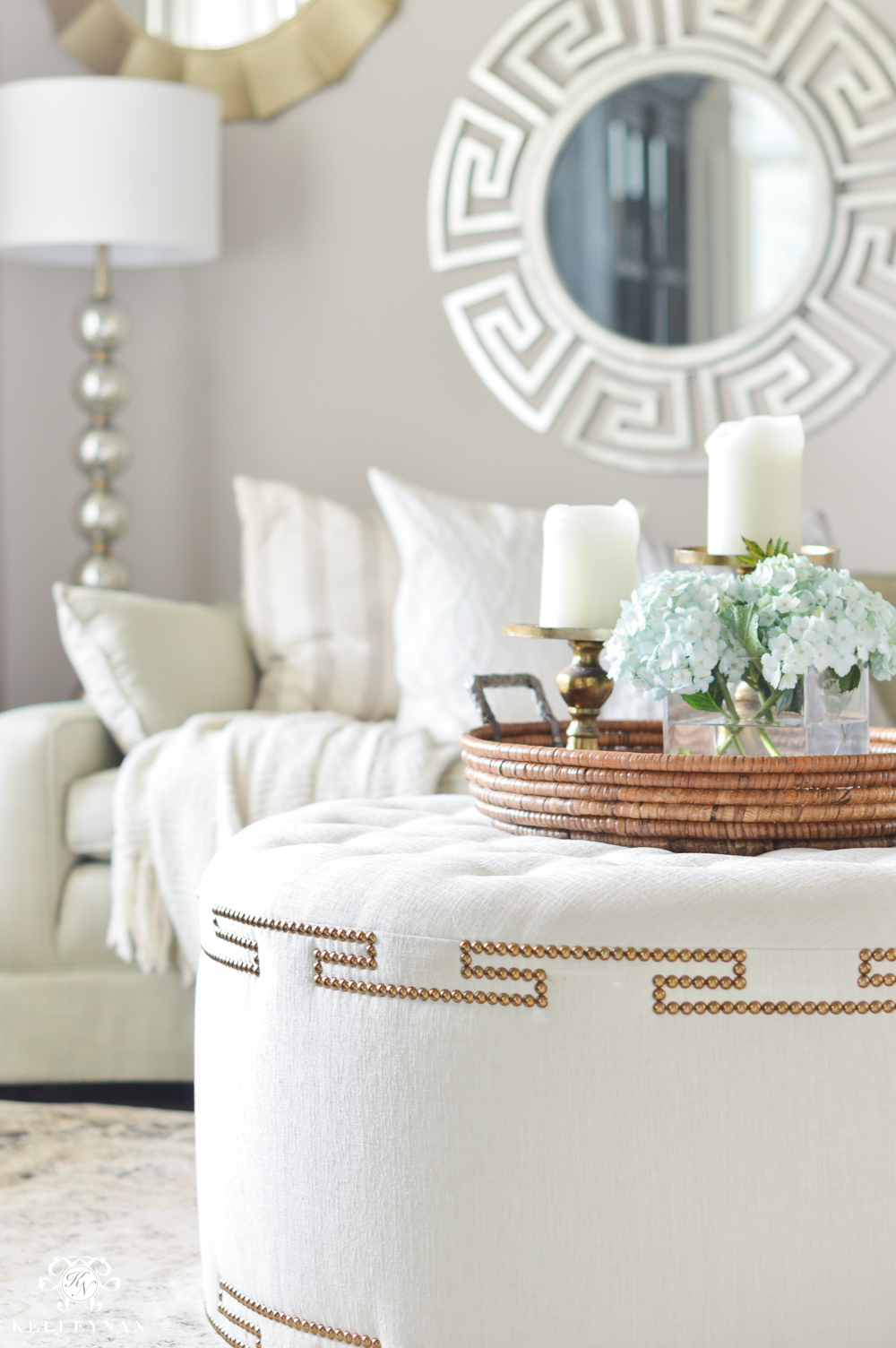 Shades of Summer Home Tour with Neutrals and Naturals-tufted coffee table ottoman in sitting room with mirror gallery wall