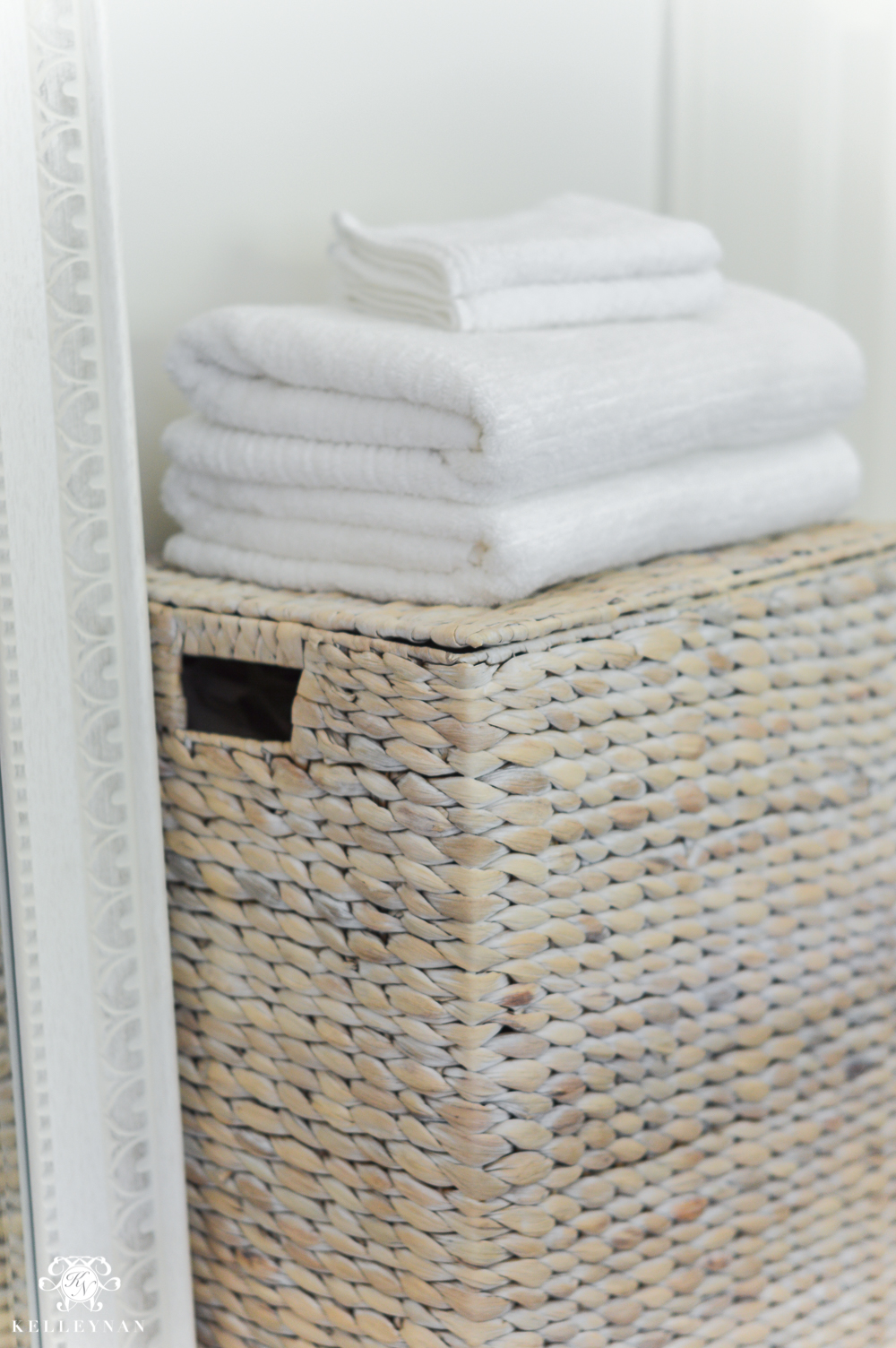 Guest Room Essentials- What every guest bedroom should have- woven hamper with white towels