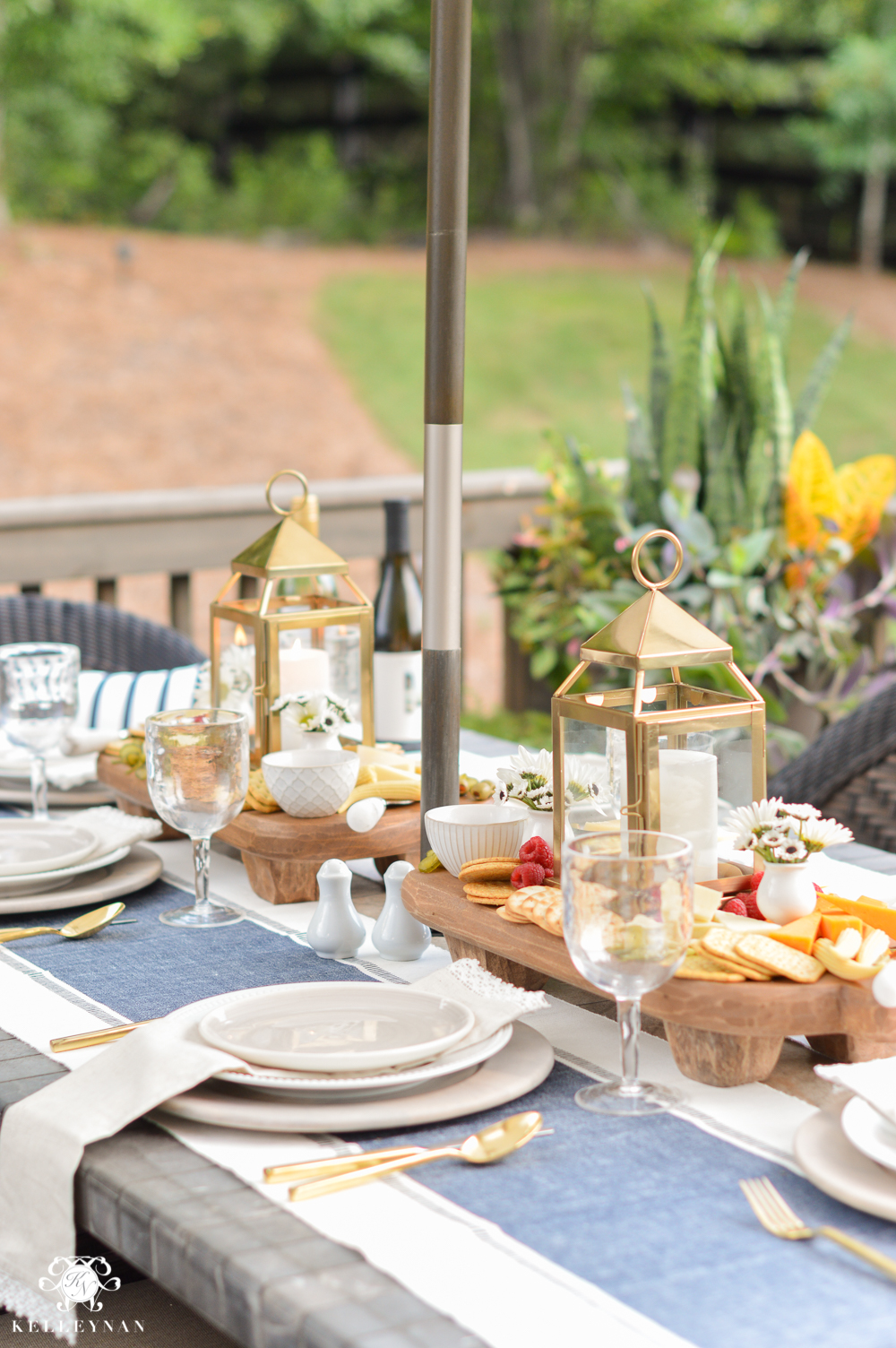 Outdoor Entertaining and Table Ideas with Cheese board appetizer centerpieces- with gold pottery barn lanterns
