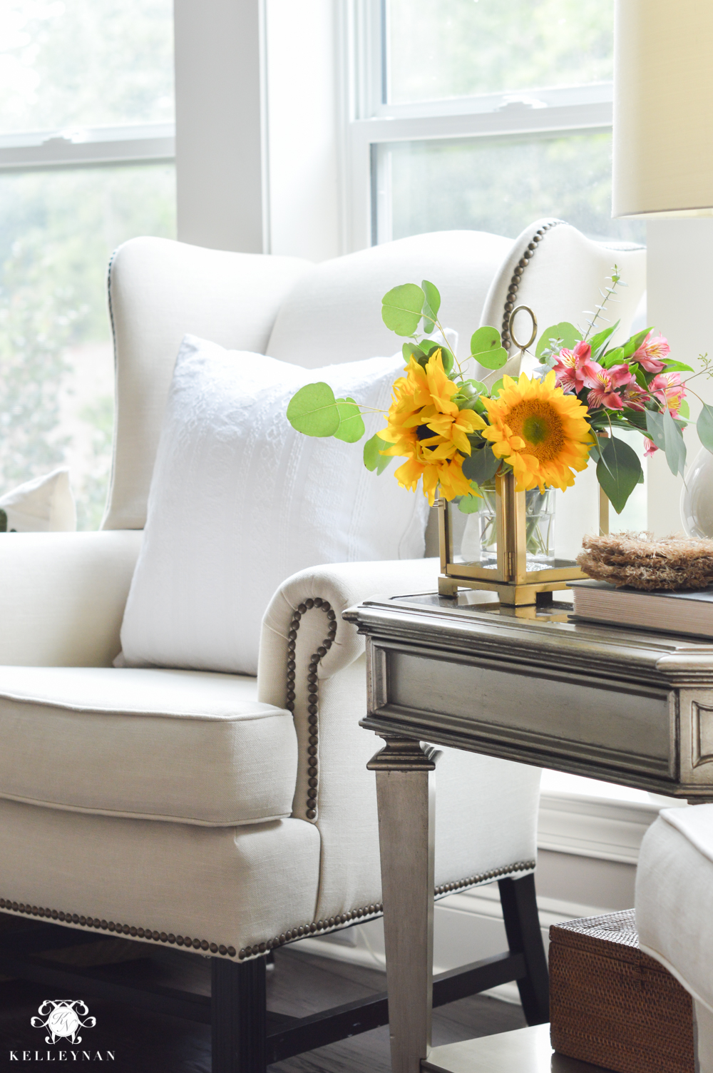 Floral Arrangement in Lantern- living room flowers in gold Pottery Barn lantern and wingback chair