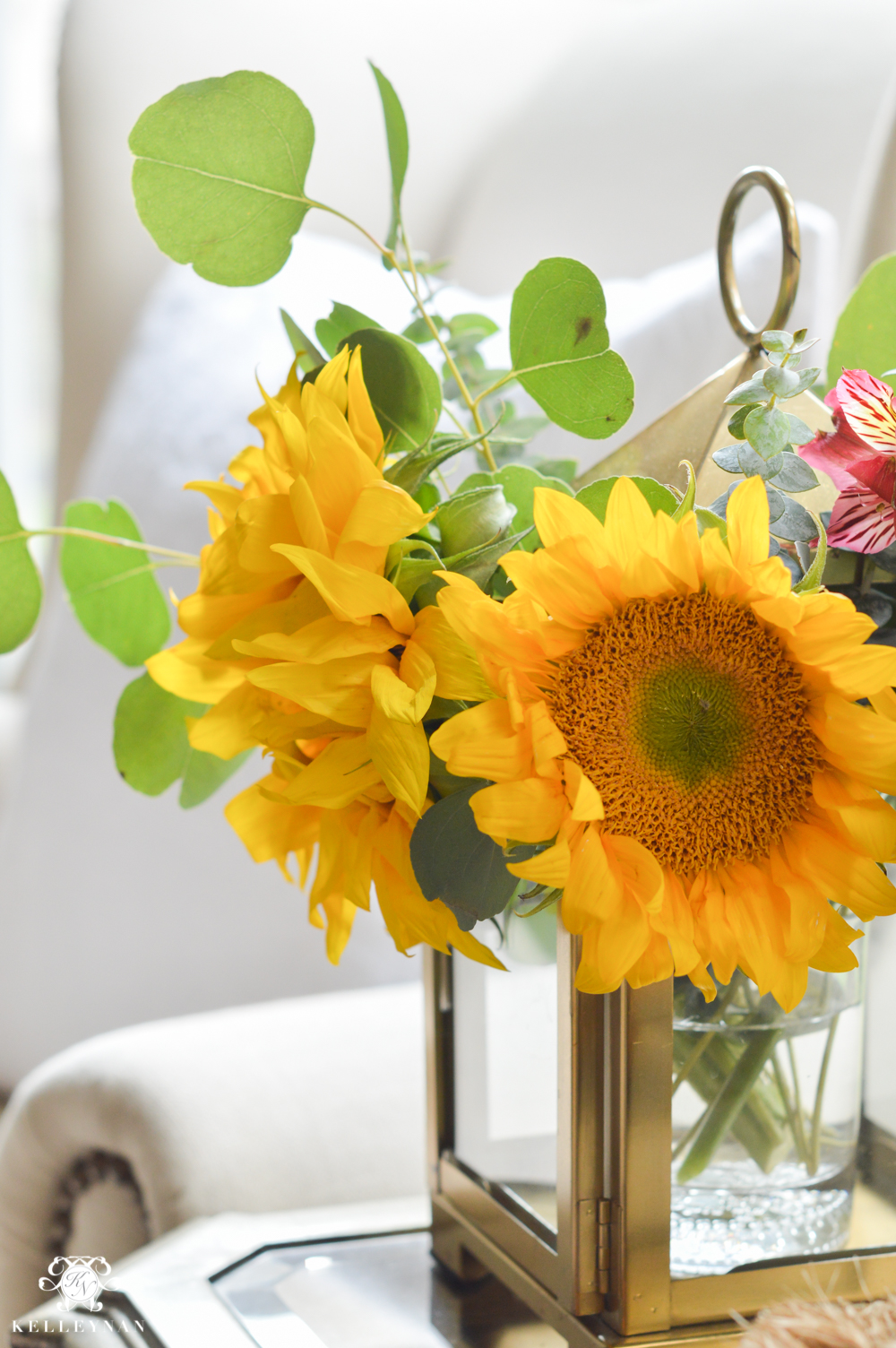 Floral Arrangement in Lantern- sunflowers and eucalyptus in small gold lantern