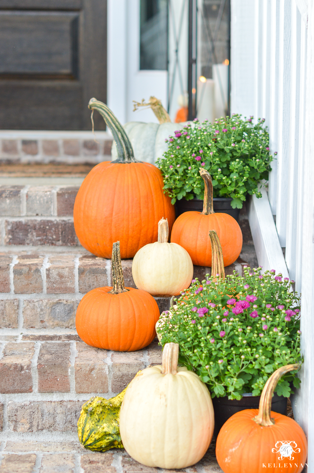 Fall front porch decor with pumpkins and purple mums