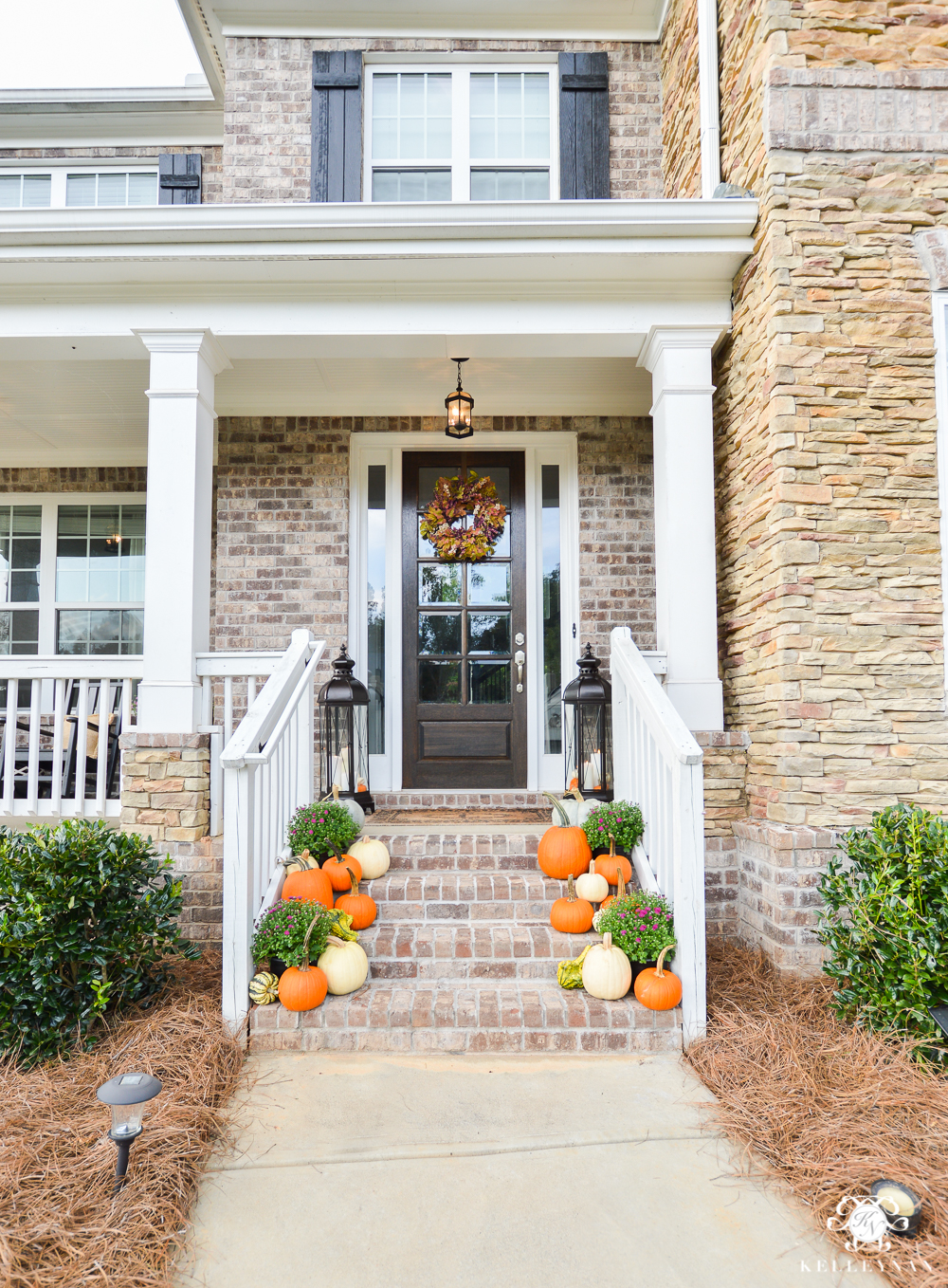 Fall front door and step decor with pumpkins and purple flowers