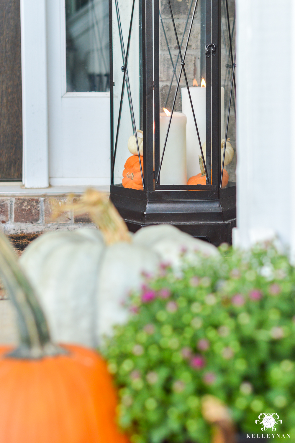 Lantern on fall front porch with candles and pumpkins