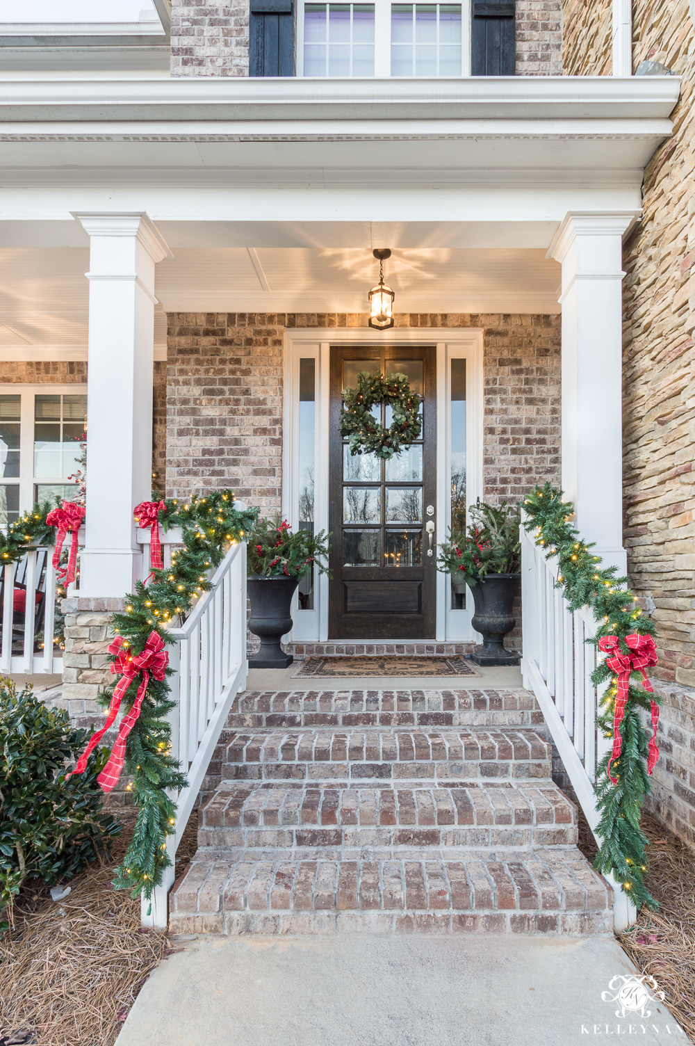 Classic Christmas front porch with green garland and red bows