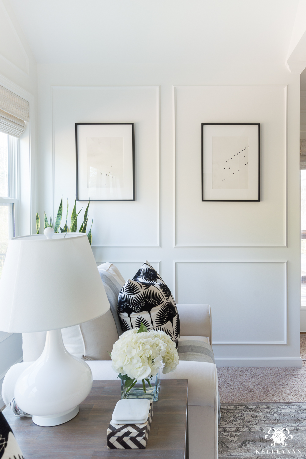 Bedroom sitting nook with white panel molding in Benjamin Moore Simply White paint