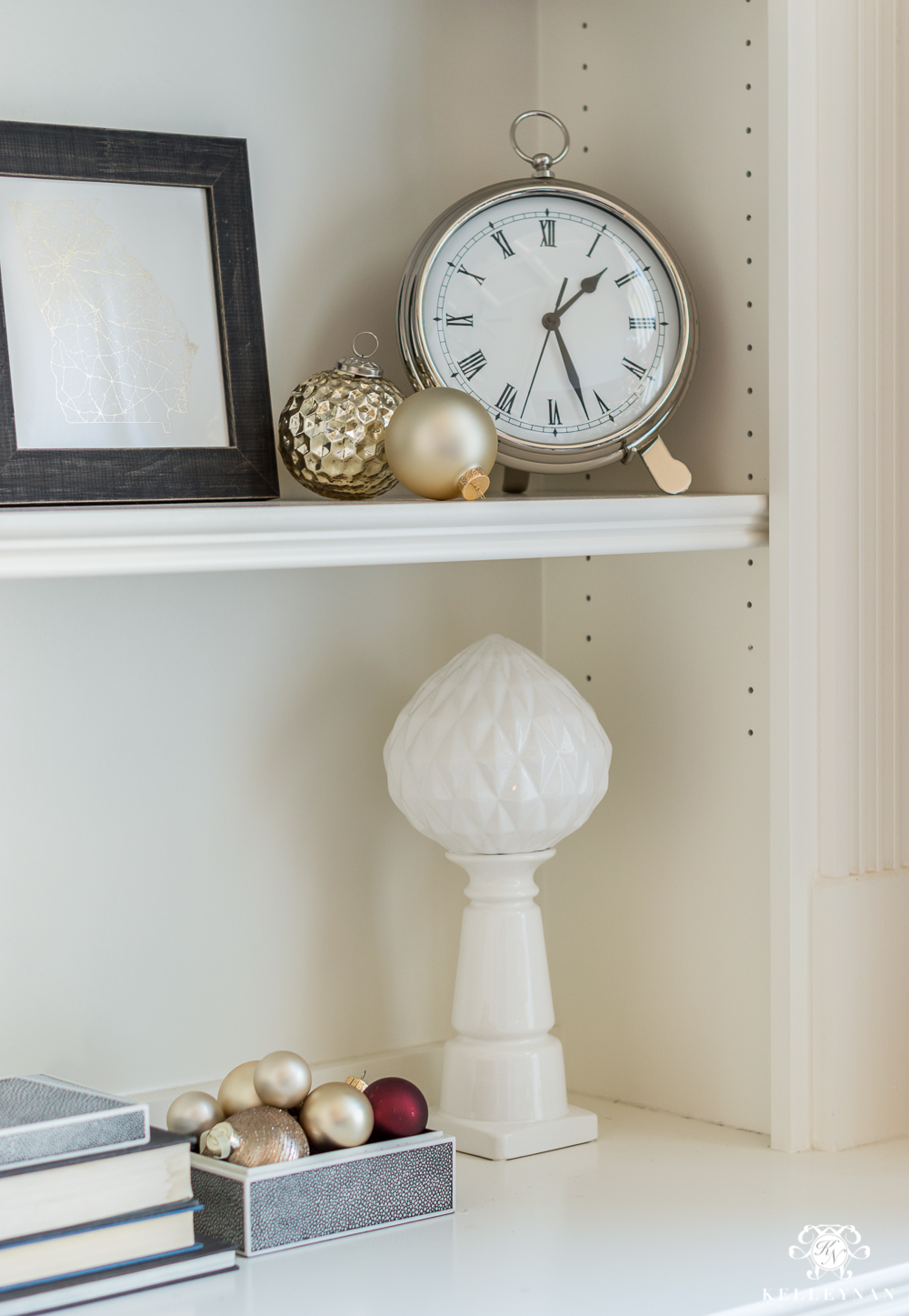 Christmas ornaments on styled bookshelves