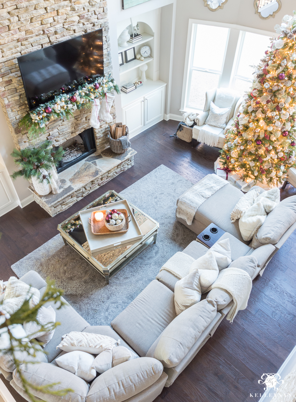 Two story Christmas living room with lazboy sectional and stacked stone fireplace