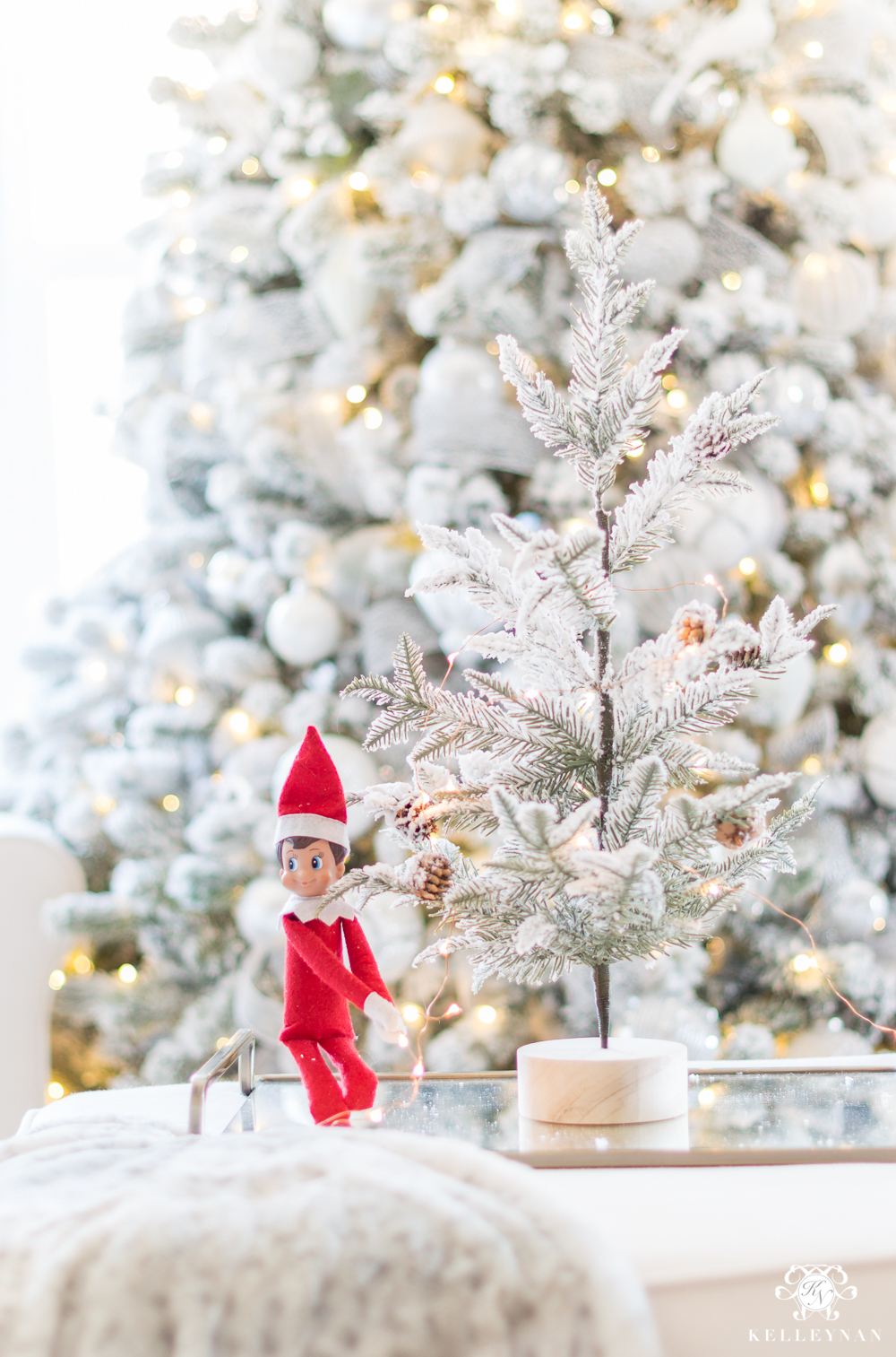 Elf on the shelf decorating a christmas tree
