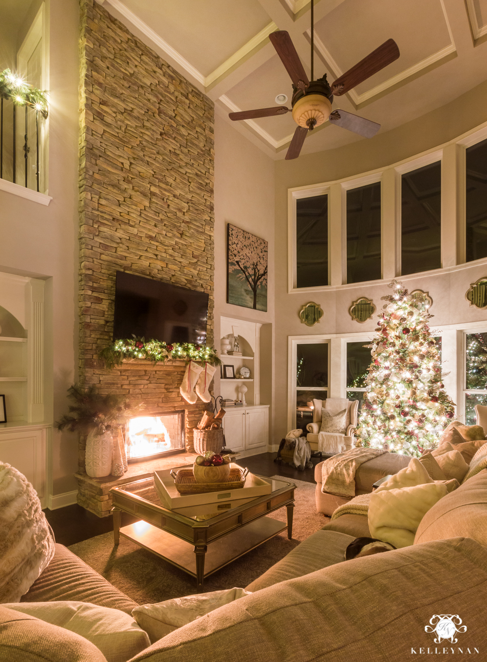 Two story christmas living room at night with fire