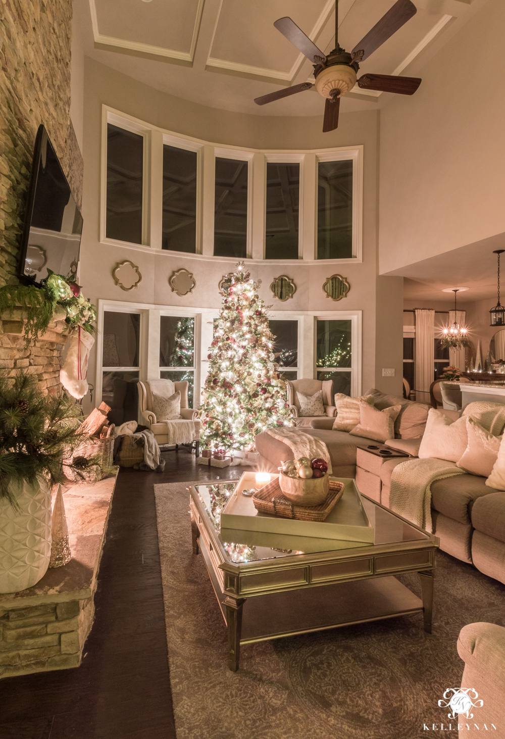 Two story living room with bay window and huge christmas tree