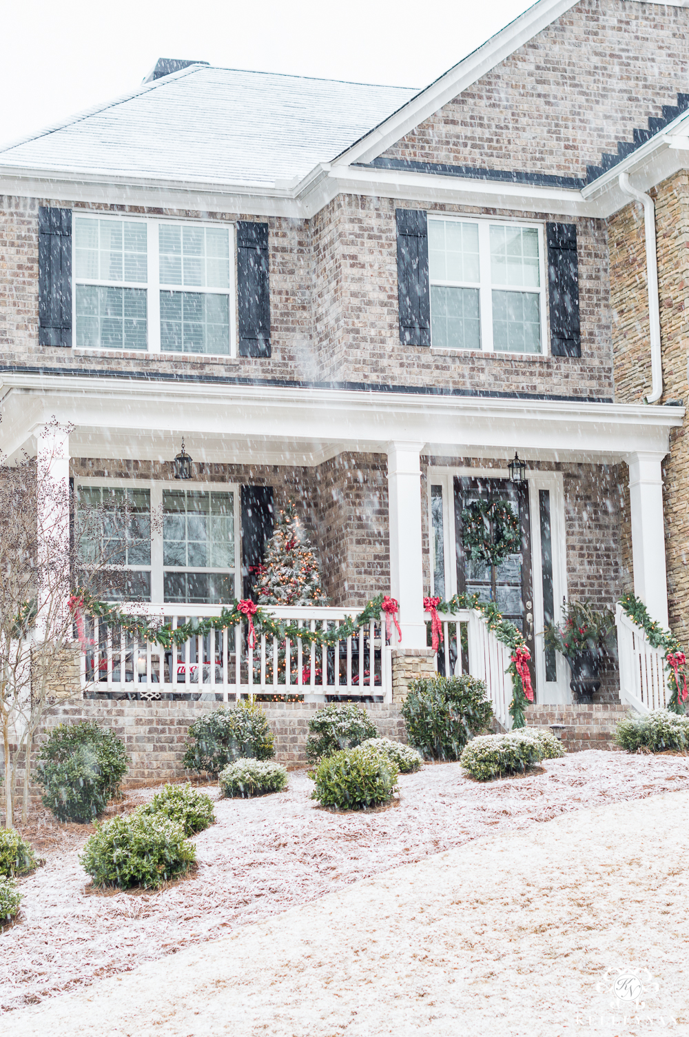 Snowy Christmas Front Porch on Brick Home with Traditional Decorations