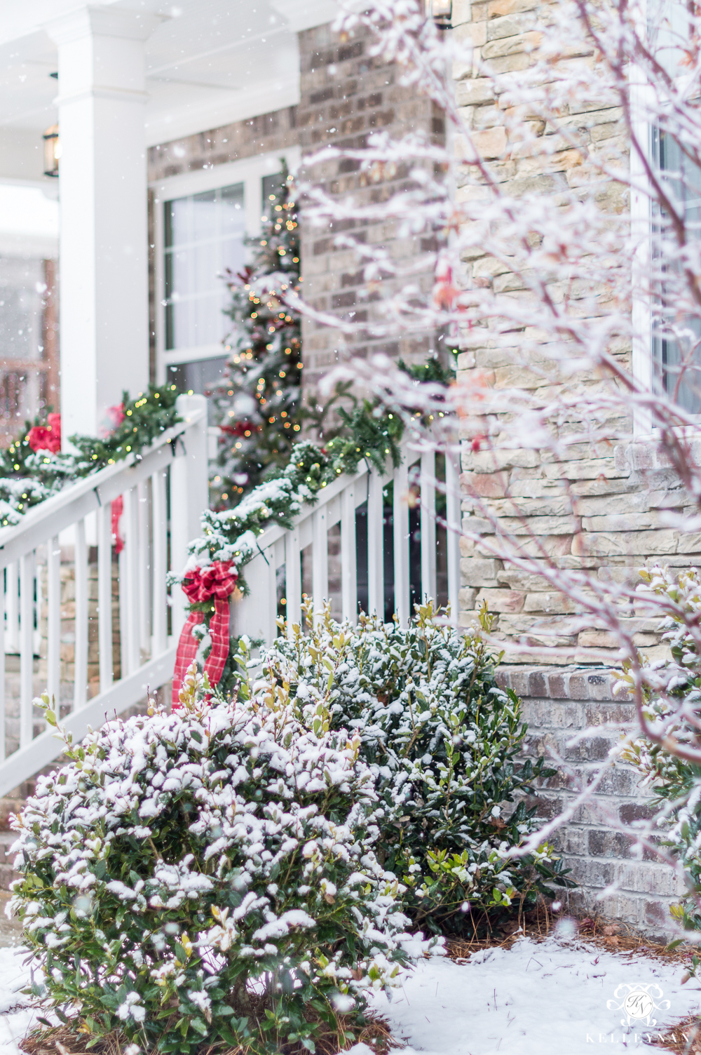 Snowy Christmas Front Porch with Red Bows on Railing
