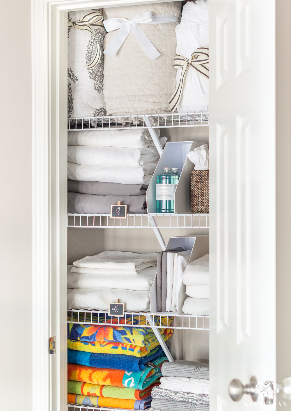 Hallway linen closet organization with comforters and bedding and beach towels