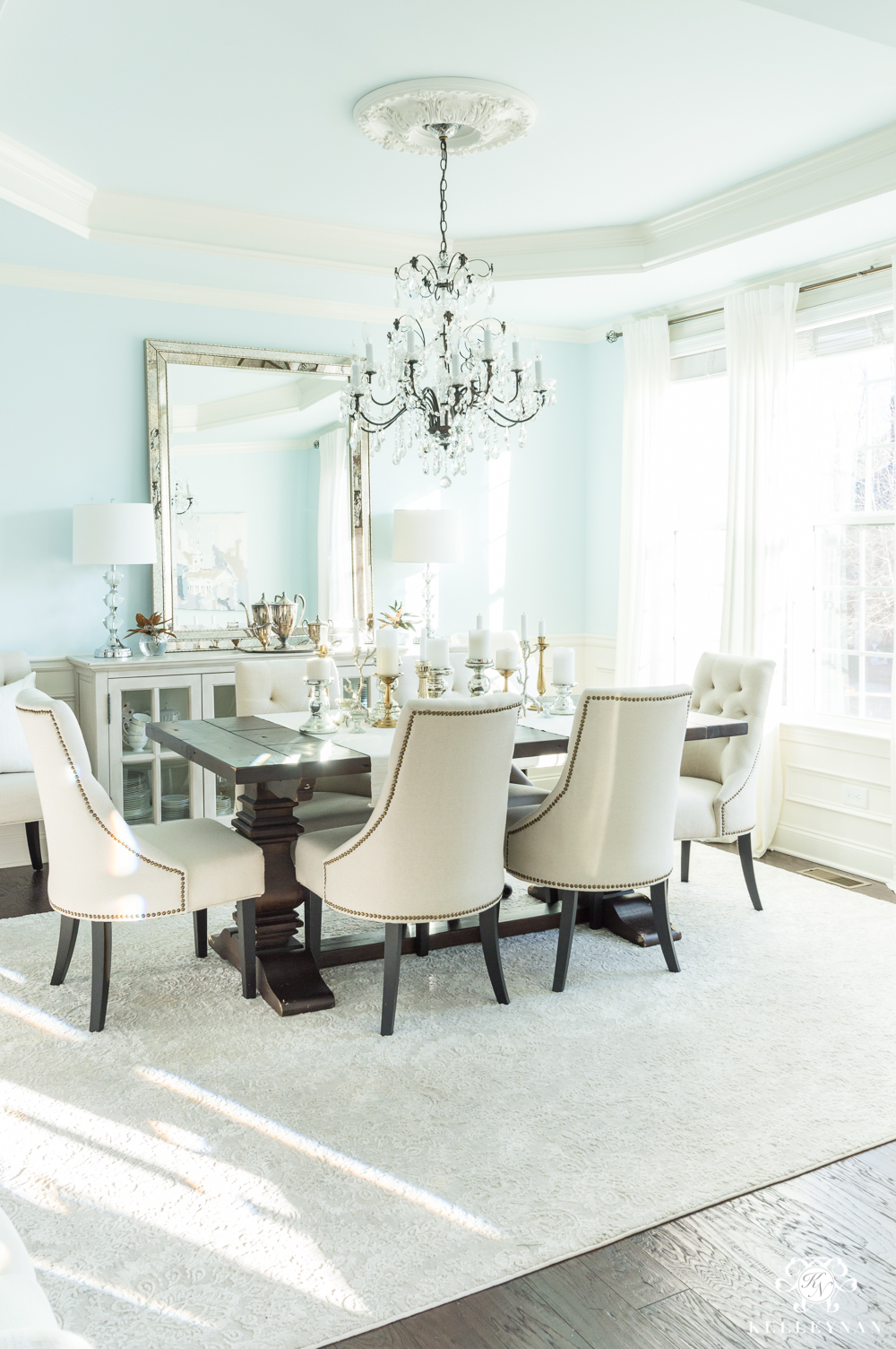 Elegant blue dining room design with cream chairs and crystal chandelier