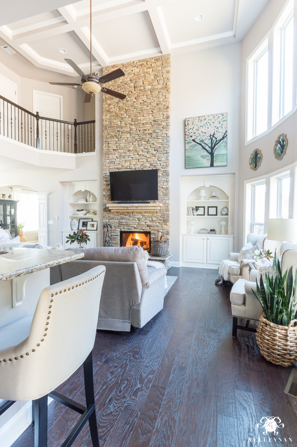 Two story living room with big stone fireplace and Versatile Gray painted walls