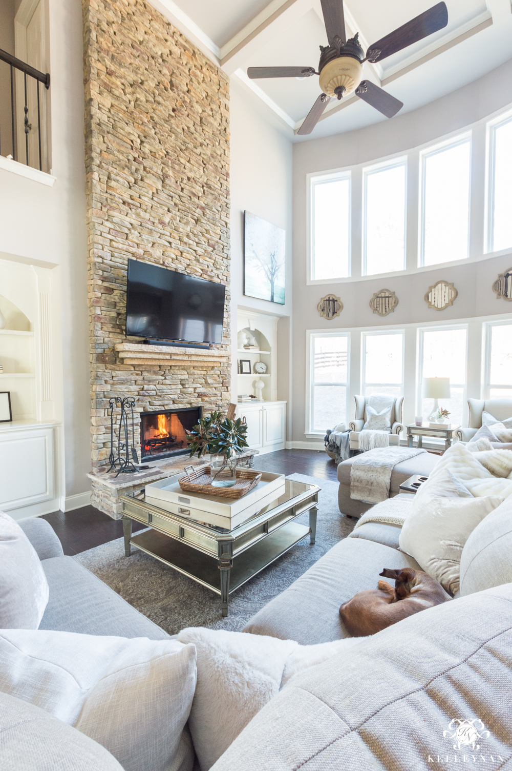 Stacked stone living room fireplace with two story row of windows
