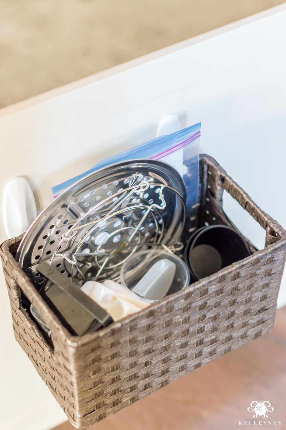 Hanging a storage basket inside the cabinet for small appliance parts