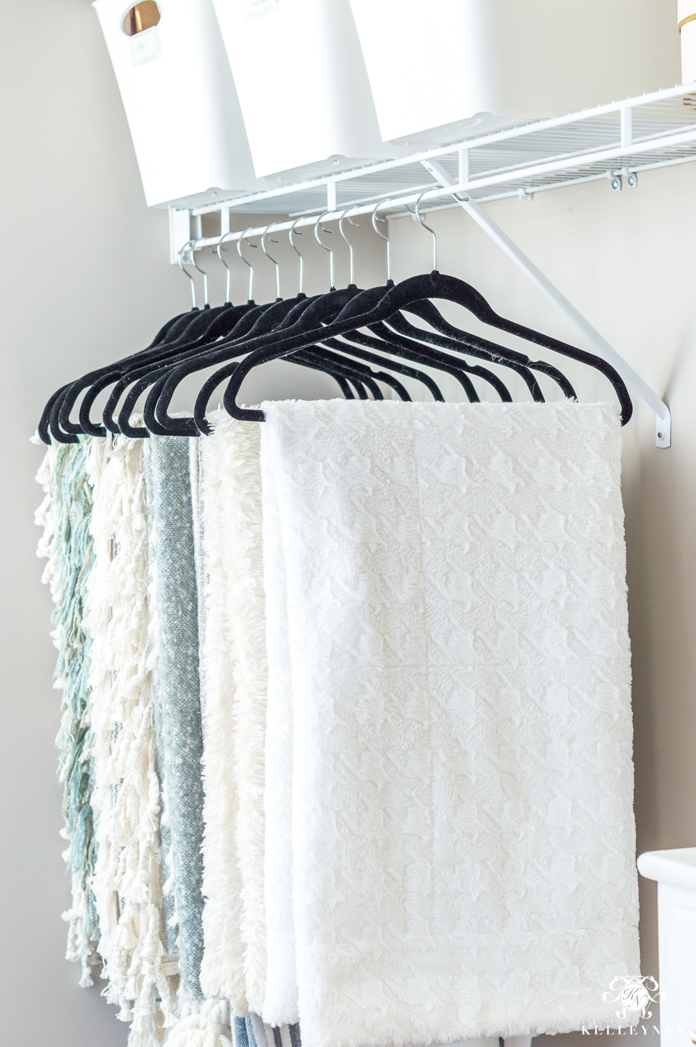 Hanging throw blankets in the closet for storage and organization