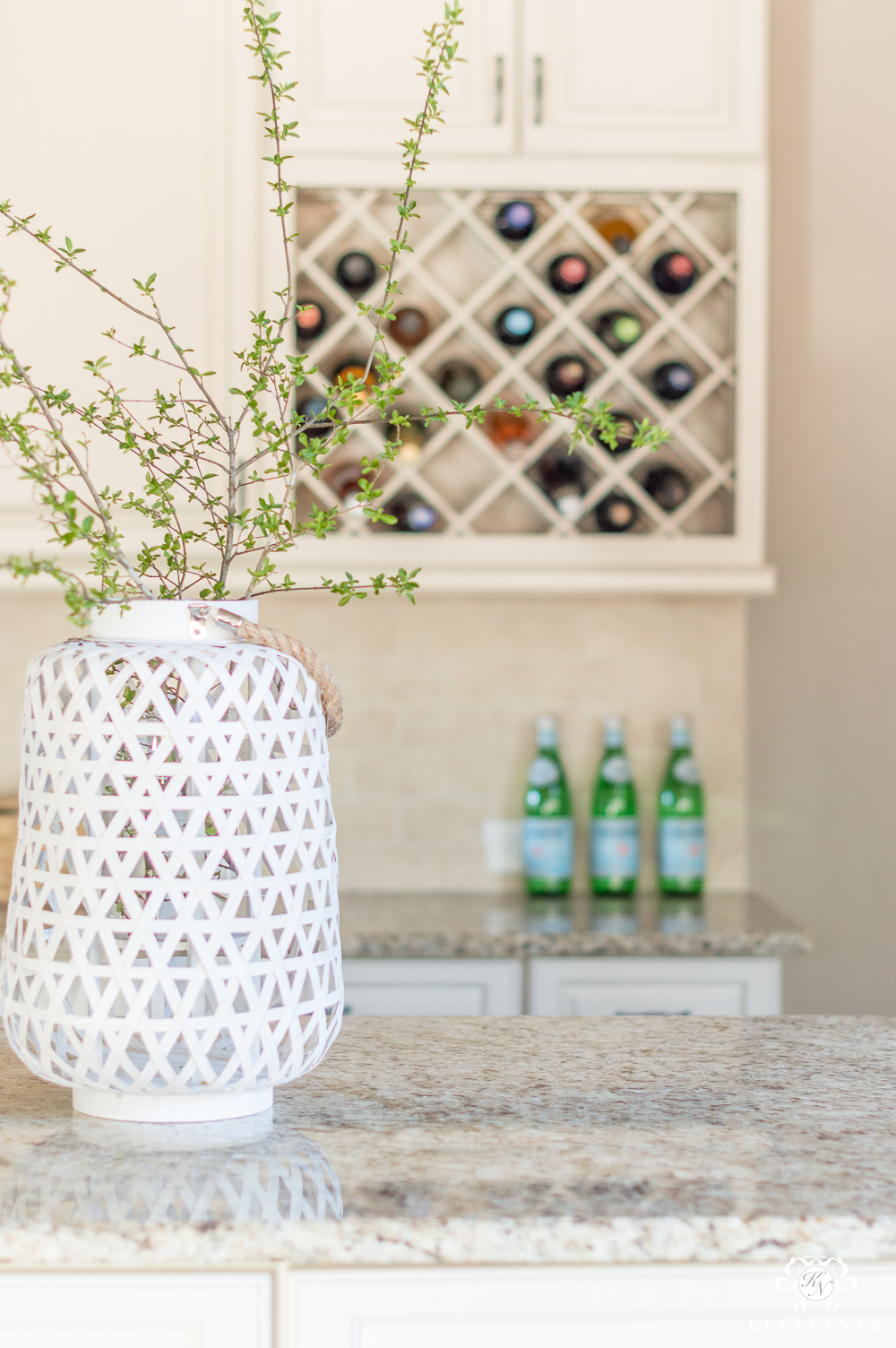 White Bamboo Lantern with Green Branches on Kitchen Island