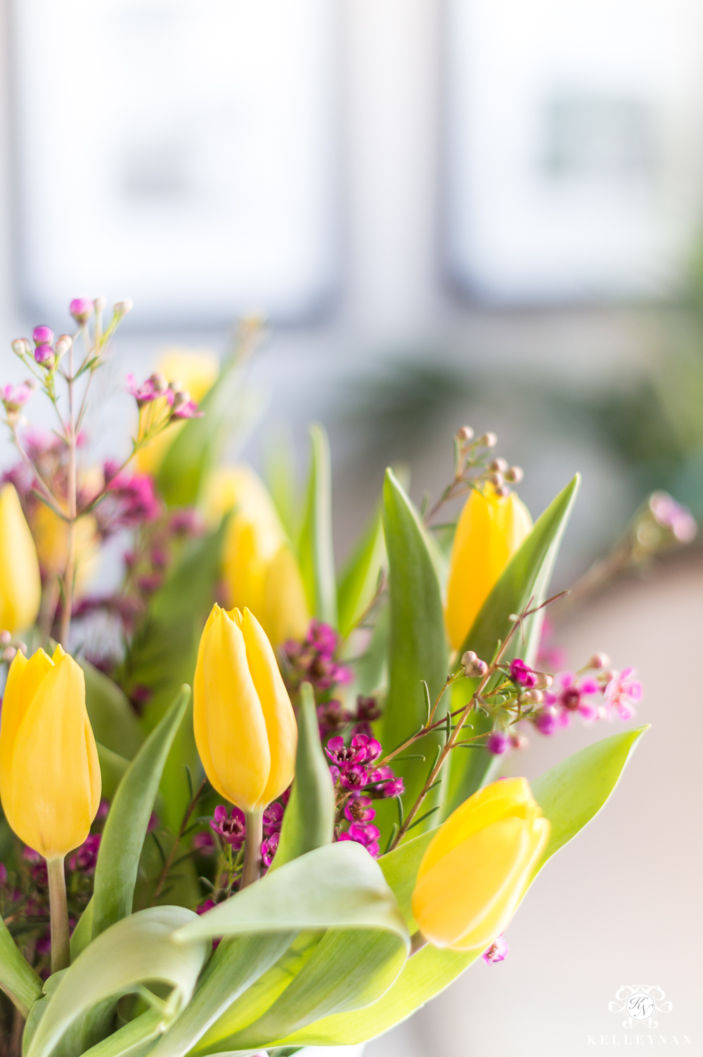 Yellow tulips and purple flowers in arrangement