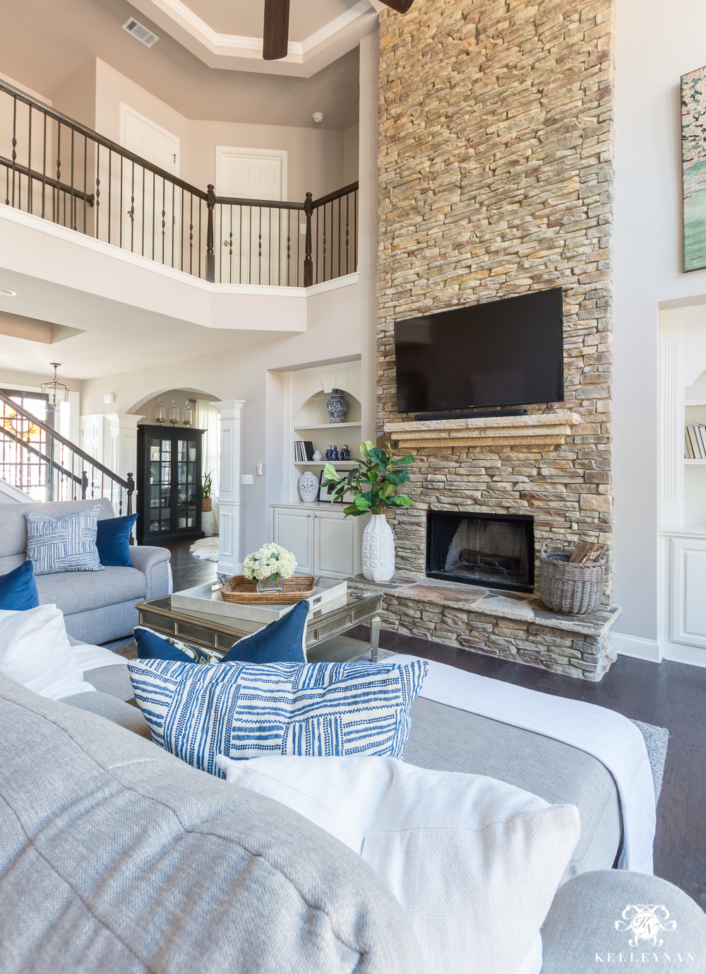 Two Story Living Room with Versatile Gray Paint and TV OVer Stacked Stone Fireplace