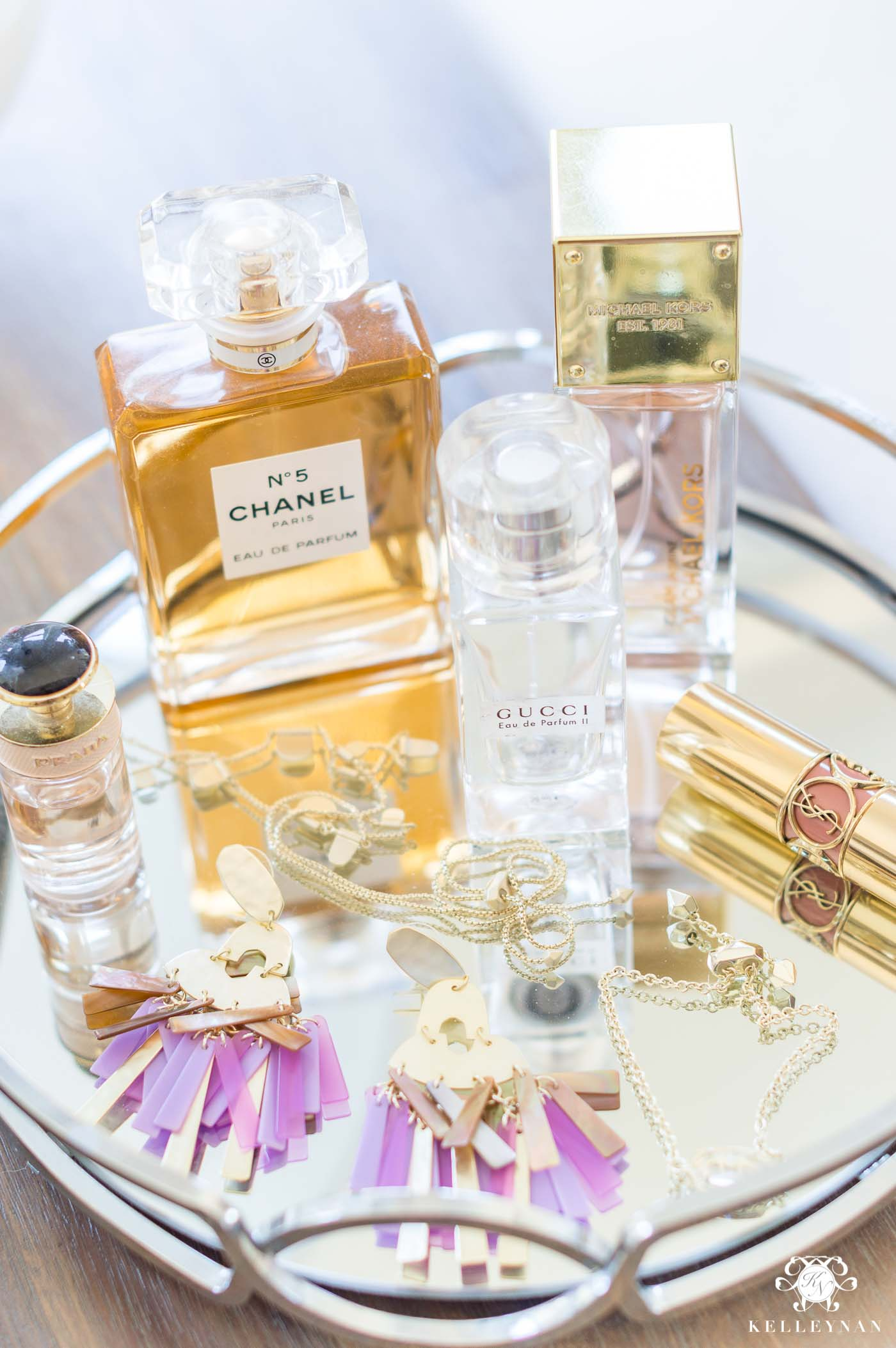 Displaying pretty perfume and jewelry on a mirrored tray in the bedroom for dresser decor