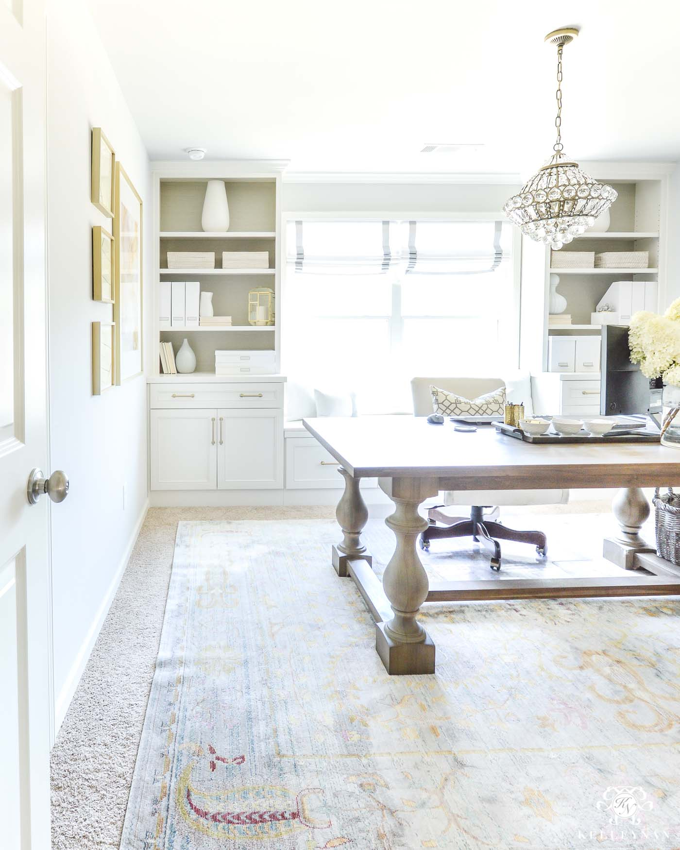 Home office with built-in shelving and chandelier