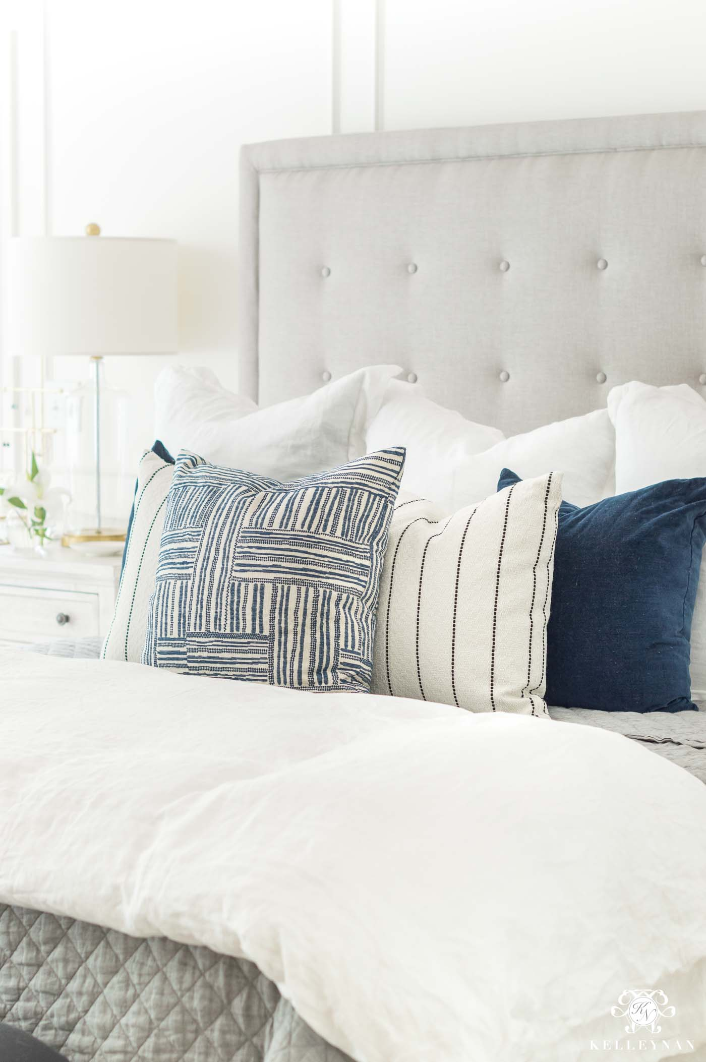 White bedding with blue and white pillows for master bedroom ideas with a tufted headboard